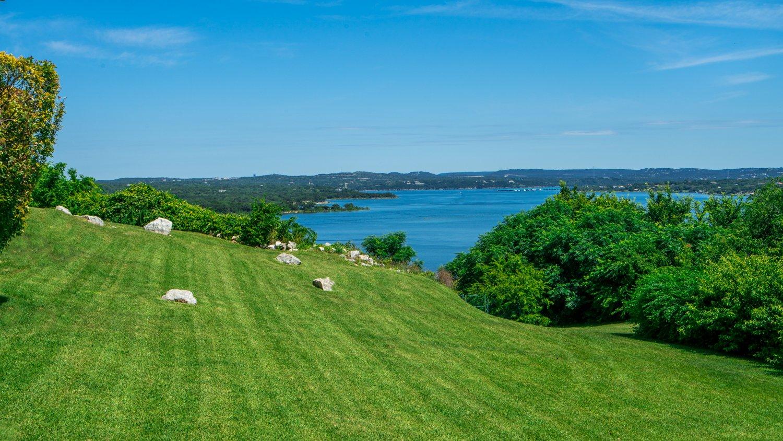 commercial-landscaping- VillasAtTravis-grass-slope-hill-shrubs-lake-1