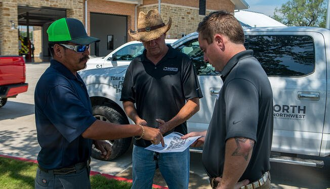 commercial landscaping crew reviewing design plan