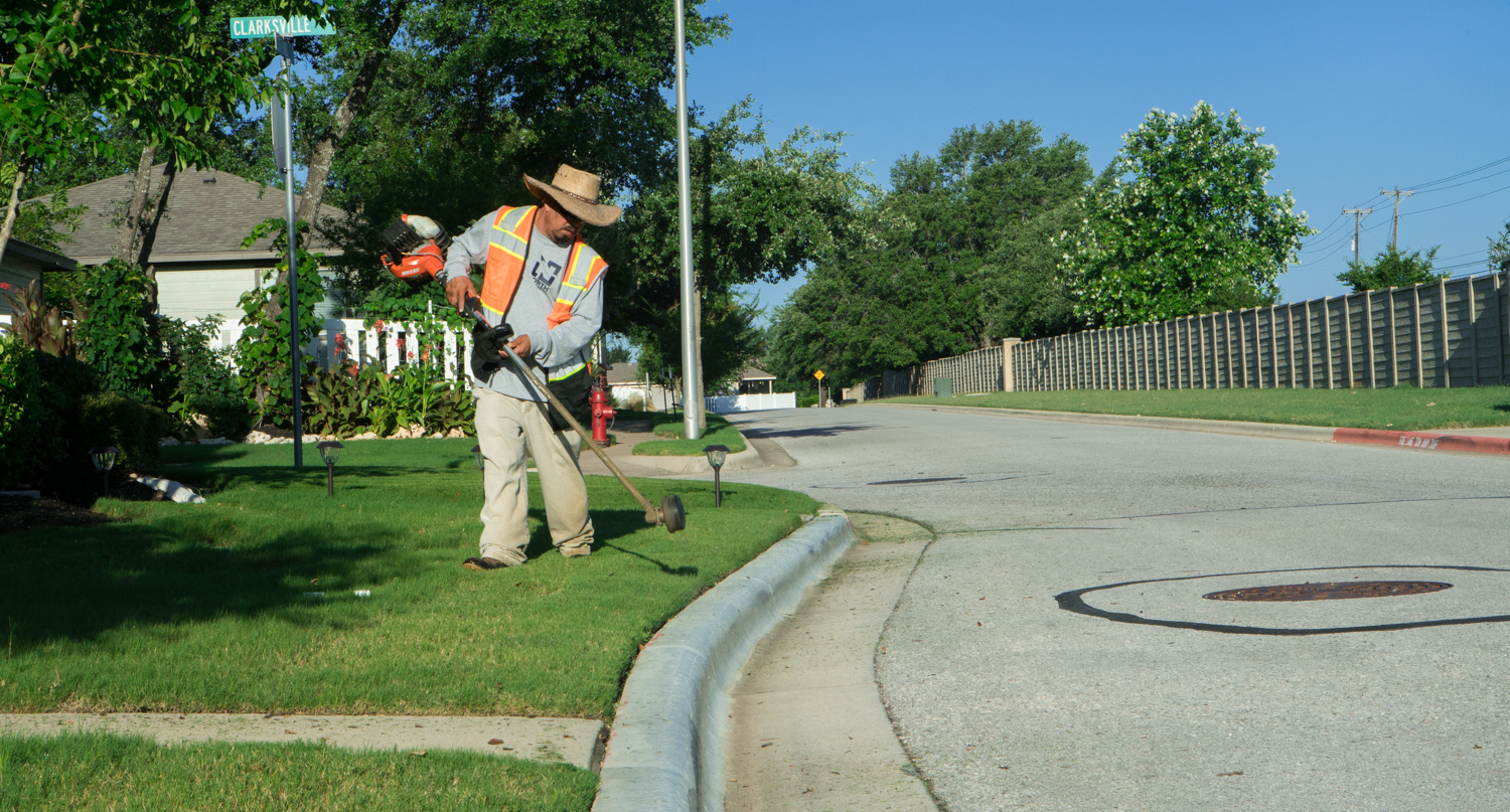 commercial landscaper trimming