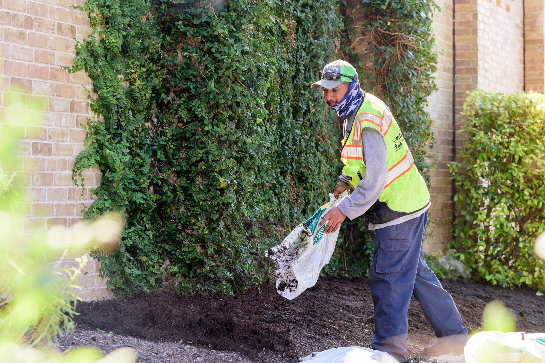 Landscape crew adding mulch to a garden bed