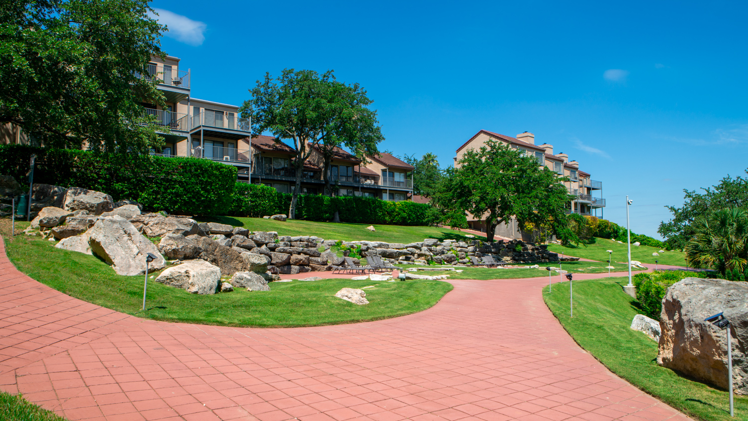 commercial-landscaping-VillasAtTravis-hill-walkway-grass-stonewall-trees-1